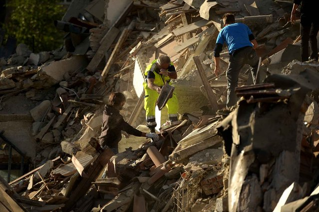 Resucers and residents clear debris in search for victims in damaged homes after a strong heathquake hit Amatrice on August 24, 2016. (Photo by Filippo Monteforte/AFP Photo)