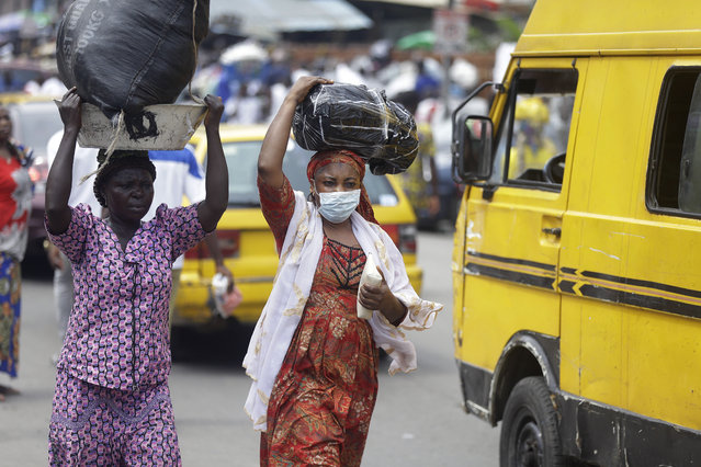 A woman wearing a face mask walks on the street, opposite the Central mosque in Lagos, Nigeria, Friday, March 20, 2020. The government banned all religious activities for four weeks following confirmation of coronavirus cases in the country. (Photo by Sunday Alamba/AP Photo)