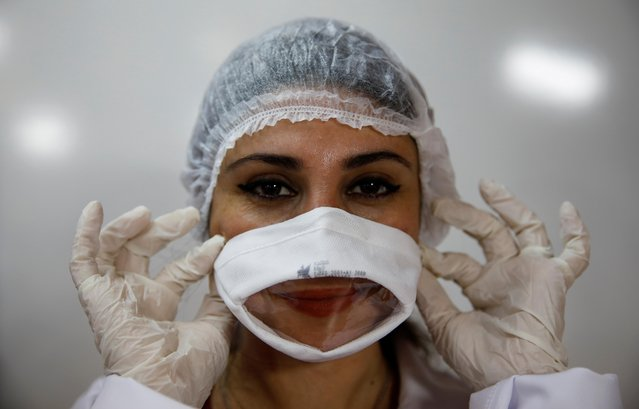 Avcilar Municipality's worker Sevim Ozek presents a protective face mask which allows lip reading, designed by Mayor Turan Hancerli for families who have hearing impaired members, in Istanbul, Turkey on May 27, 2020. (Photo by Umit Bektas/Reuters)