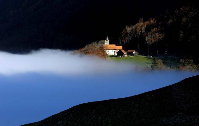 Fog covers a valley near Sachseln, Switzerland, November 16, 2012. (Photo by Urs Flueeler/Keystone)
