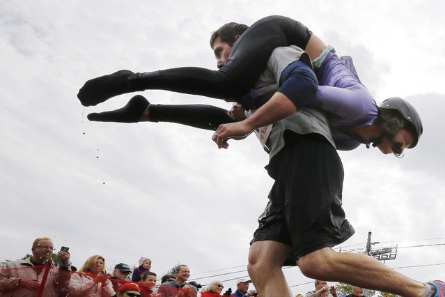 Nathan Johnson carries Tia Johnson out of the water pit while competing in the North American Wife Carrying Championship at Sunday River ski resort in Newry, Maine October 11, 2014. REUTERS/Brian Snyder
