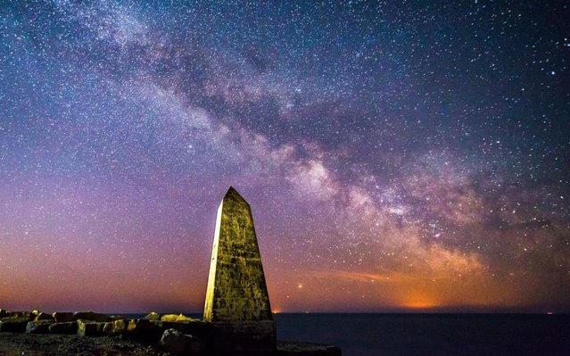 The Milky Way glows brightly in the clear night sky above the obelisk at Portland Bill in Dorset, England on March 25, 2020. (Photo by Graham Hunt/Alamy Live News)