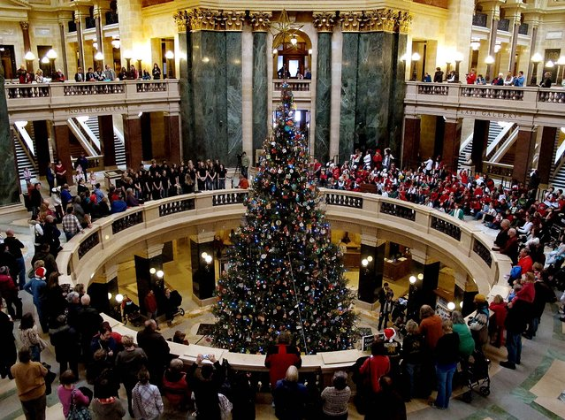 Fourth-graders from Medford Elementary and Stetsonville Elementary schools perform during a Christmas tree lighting ceremony at the State Capitol in Madison, Wisconsin. (Photo by Scott Bauer/Associated Press)