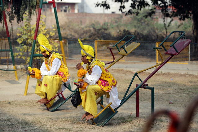"Indian young men wearing traditional folk dance ""Bhangra"" attire of Punjab, sit on see-saws and sip on soft drinks at a park before their performance during the Khalsa College International Folk Festival 2017 in Amritsar, India, 29 November 2017. The festival is aimed to promote cultural ties between India and participating countries. (Photo by Raminder Pal Singh/EPA/EFE)"