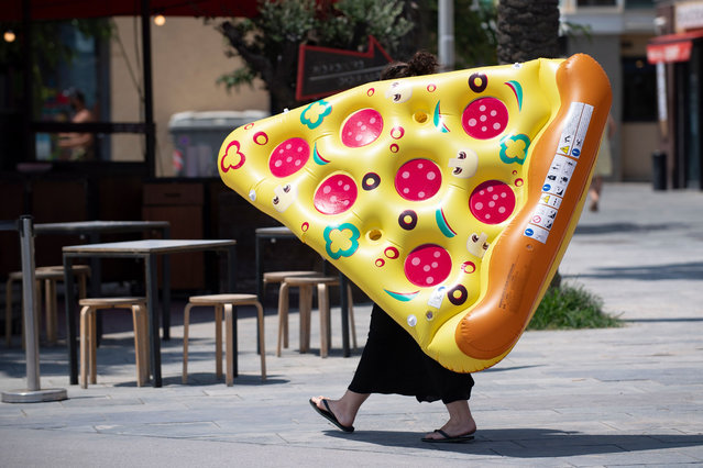 A woman carries an inflatable float with the sahpe of a portion of pizza in a Barcelona, on July 18, 2020. Four million residents of Barcelona have been urged to stay at home as virus cases rise, while EU leaders were set to meet again in Brussels, seeking to rescue Europe's economy from the ravages of the pandemic. (Photo by Josep Lago/AFP Photo)
