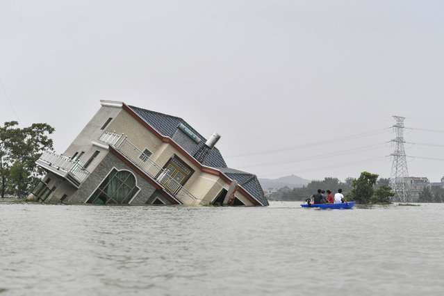 This photo taken on July 15, 2020 shows residents riding a boat past a damaged and flood-affected house near the Poyang Lake due to torrential rains in Poyang county, Shangrao city in China's central Jiangxi province. The vast Yangtze drainage area has been lashed by torrential rains since last month, leaving 141 people dead or missing and forcing the evacuation of millions more across several provinces. (Photo by AFP Photo/China Stringer Network)