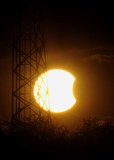 A partial solar eclipse is visable through a cell tower just before sunset Thursday, October 23, 2014, in Martinsburg, W.Va. (Photo by Ron Agnir/AP Photo/The Journal)