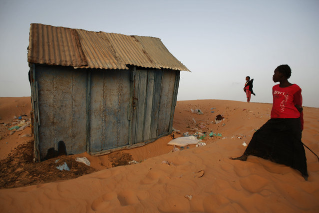 Girls stand near a house built on top of a dune in the poor neighborhood of Hay Sakin, in Nouakchott, Mauritania Friday July 17, 2009. (Photo by Rebecca Blackwell/AP Photo)