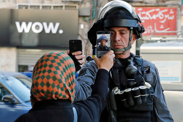 A Palestinian woman takes a picture of a member of the Israeli security forces as he takes her picture in a street in Jerusalem on December 16, 2017, as demonstrations continue to flare in the Middle East and elsewhere over the US president' s declaration of Jerusalem as Israel' s capital. (Photo by Ahmad Gharabli/AFP Photo)