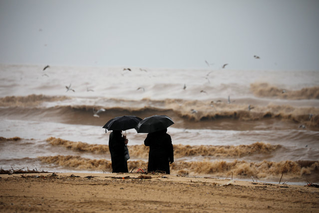 Ultra-Orthodox Jewish men hold umbrellas and look at the Mediterranean Sea as heavy rainfalls hit Israel, in Ashdod, Israel on January 9, 2020. (Photo by Amir Cohen/Reuters)