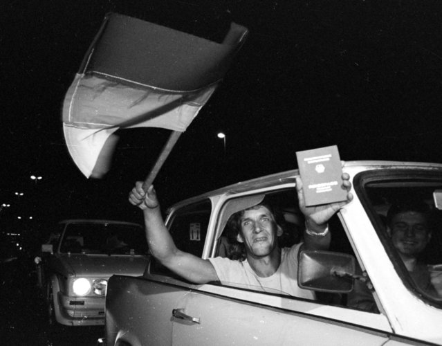 An East German refugee shows off a newly acquired West German passport just before crossing the Hungarian border in to Austria, September 10, 1989. (Photo by Reuters)