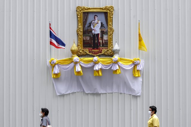 People wearing protective face masks walk past a portrait of Thai King Maha Vajiralongkorn Bodindradebayavarangkun (Thai King Rama X) outside a construction site in honor of his upcoming 68th birthday in Bangkok, Thailand, 22 July 2020. Thais across the country will observe the 68th birthday of Maha Vajiralongkorn Bodindradebayavarangkun on 28 July 2020. (Photo by Diego Azubel/EPA/EFE)