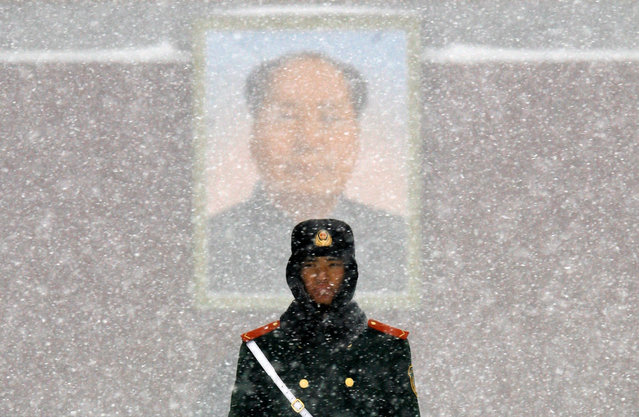 A paramilitary policeman stands guard in front of the giant portrait of former Chinese Chairman Mao Zedong, on a snow-covered Tiananmen Square in Beijing January 3, 2010. (Photo by David Gray/Reuters)