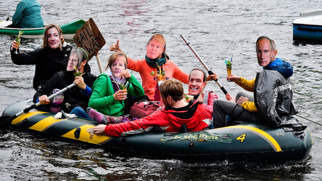 Protestors with masks of politicians drink cocktails in a boat on the Alster river during a demonstration called by several NGOs ahead of the G20 summit in Hamburg on July 2, 2017. (Photo by John MacDougall/AFP Photo)