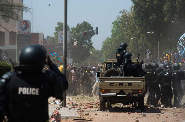 In this file photo Tuesday, October 28, 2014, Burkina Faso Police clash with protesters as they protest against their longtime president that seeks another term in Ouagadougou, Burkina Faso. (Photo by Theo Renaut/AP Photo)