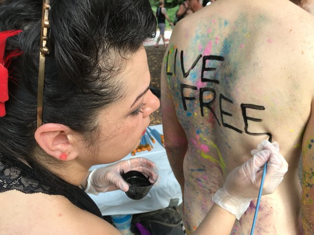 Artist Nicole Tossas paints a slogan on the back of a bicyclist before the annual Philly Naked Bike Ride in Philadelphia on Saturday September 10, 2016. Thousands of bicyclists dared to be bare for the city's annual nude ride promoting positive body image, cycling advocacy and fuel conservation. (Photo by Dino Hazell/AP Photo)