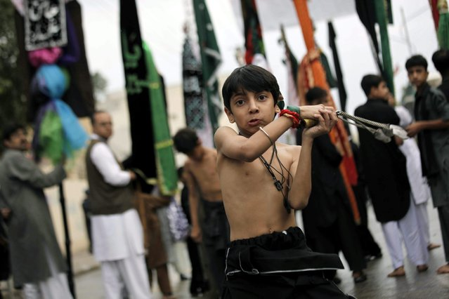 A Pakistani Shiite Muslim boy flagellates himself with chains, a day ahead of Ashura, the tenth day in the month of Muharram, in Peshawar, Pakistan, 3 November 2014. (Photo by Bilawal Arbab/EPA)
