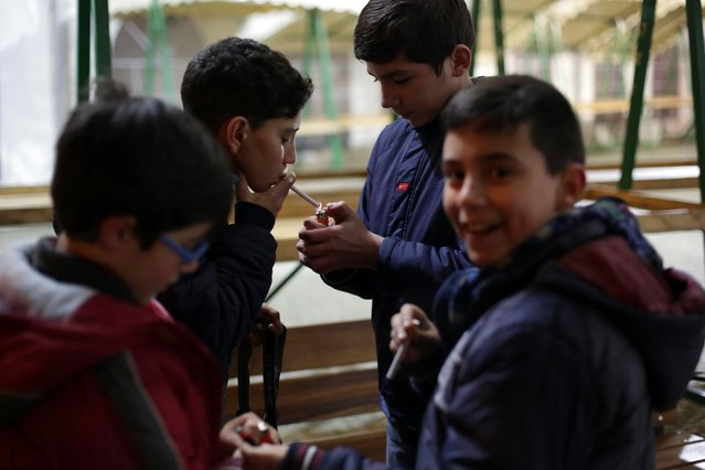 Young boys light cigarettes in the village of Vale de Salgueiro, northern Portugal, during the local Kings' Feast Friday, January 5, 2018. (Photo by Armando Franca/AP Photo)