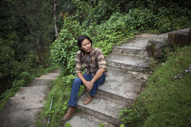 In this Thursday, September 25, 2014 photo, exile Tibetan Tsering Choephel, 26, rests on concrete stairs in Dharmsala, India. Choephel left his home in Tibet 23 years ago. Sometimes, he dreams of seeing his family again. Often, he mourns the fact that he barely misses them. (Photo by Tsering Topgyal/AP Photo)