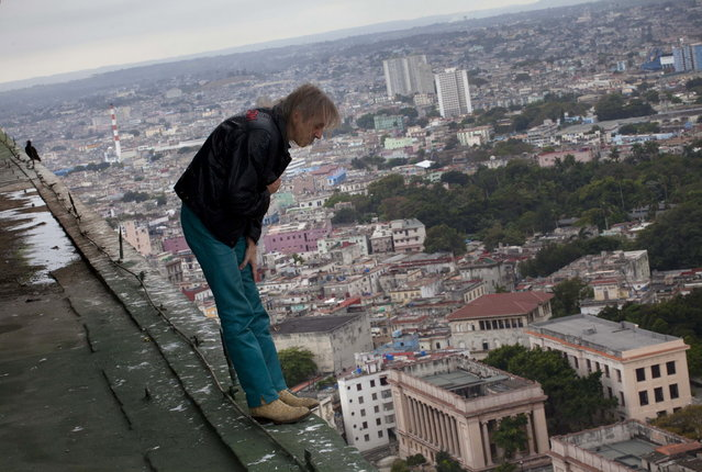 "Alain Robert known as ""Spiderman"", looks over the edge from the roof of the Habana Libre hotel in Havana, Cuba, Friday, February 1, 2013. Robert, from France, plans to climb the 27 floor hotel on Monday. (AP Photo/Ramon Espinosa)"