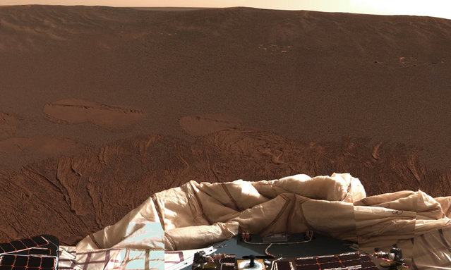 The interior of a crater surrounding the Mars Exploration Rover Opportunity at Meridiani Planum on Mars can be seen in this color image from the rover's panoramic camera, on January 24, 2004. Note the disturbances in the soil from the airbags, which were used to cushion the landing. The airbags are now deflated, seen at bottom. (Photo by NASA/JPL/Cornell/The Atlantic)