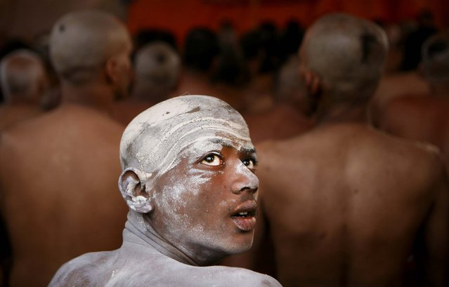A man watches as other Hindu holy men of the Juna Akhara sect participate in a rituals that are believed to rid them of all ties in this life and dedicate themselves to serving God, on February 6, 2013. (Photo by Rajesh Kumar Singh/Associated Press)