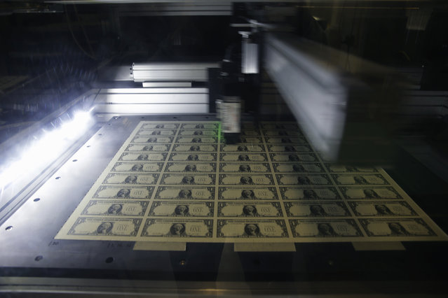 A sheet of one dollar bills is scanned for quality during production at the Bureau of Engraving and Printing in Washington November 14, 2014. (Photo by Gary Cameron/Reuters)