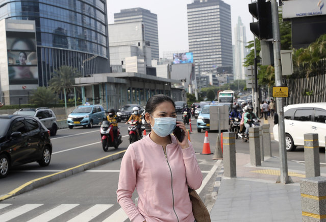 A woman, wearing a face mask as a precaution against the new coronavirus outbreak, talks on her mobile phone on the sidewalk of a street at the main business district in Jakarta, Indonesia, Monday, September 14, 2020. Indonesia's capital on Monday begins to reimpose large-scale social restrictions to control a rapid expansion in the virus cases. (Photo by Tatan Syuflana/AP Photo)
