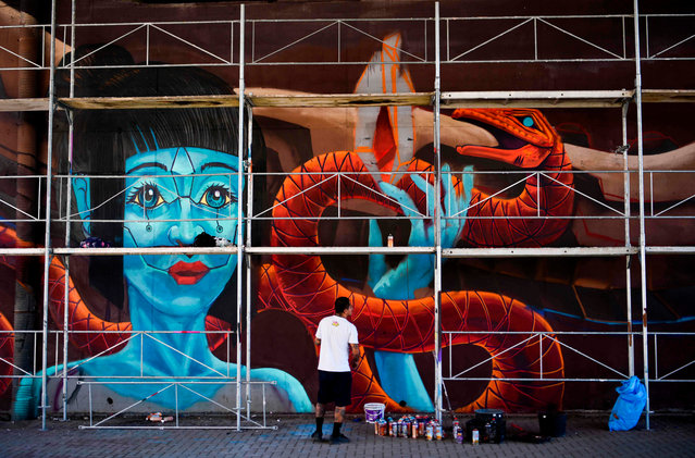 "This photograph taken on September 1, 2020, shows a Mexican graffiti artist working on his piece during the graffiti festival ""Meeting Of Styles"", in Pristina. The International Meeting of Styles (MOS) is an international network of graffiti artists and aficionados that began in Wiesbaden, Germany, in 2002. (Photo by Armend Nimani/AFP Photo)"