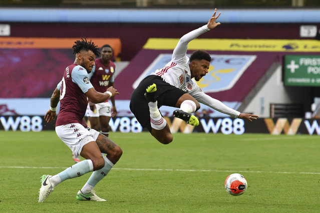 Sheffield United's Mbwana Samatta, right, is tackled by Aston Villa's Tyrone Mings during the English Premier League soccer match between Aston Villa and Sheffield United at Villa Park in Birmingham, England, Wednesday, June 17, 2020. The English Premier League resumes Wednesday after its three-month suspension because of the coronavirus outbreak. (Photo by Paul Ellis/Pool via AP Photo)