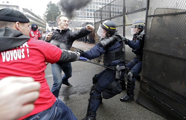 Protesters scuffle with French riot police in front of the headquarters of tire maker Goodyear Dunlop France during a demonstration against job cuts March 7, 2013  near Paris. In January, Goodyear confirmed plans to close a French plant near the northern city of Amiens, which would cut 1,173 jobs. (Photo by Jacky Naegelen/Reuters)