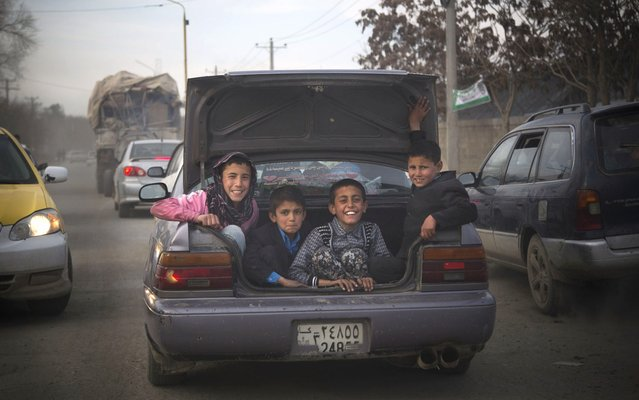 Afghan boys peer out from the trunk of a car as they get a ride through the center of Kabul, Friday, March 15, 2013. (Photo by Anja Niedringhaus/AP Photo)