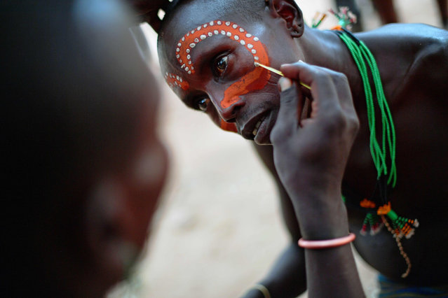 """A Hamar man has his face painted before a bull jumping ceremony in Ethiopia's southern Omo Valley region near Turmi on September 19, 2016. The Hamar are a Nilotic ethnic group in Ethiopia. Bull jumping has been practised by the Hamars for thousands of years. The ceremony is a coming of age tradition which allows young men to marry. The man has to run across the backs of bulls which have been lined up, 4 times. If he falls through the row of bulls he is to start again until he finishes without falling. If the man fails to properly """"jump the bulls"""" he risks humiliation and being cast out by his village as well as never being able to marry in the future. Before the ceremony women line up to be whipped by men holding sticks to prove their devotion to the men. The construction of the Gibe III dam, the third largest hydroelectric plant in Africa, and large areas of very """"thirsty"""" cotton and sugar plantations and factories along the Omo river are impacting heavily on the lives of tribes living in the Omo Valley who depend on the river for their survival and way of life. Human rights groups fear for the future of the tribes if they are forced to scatter, give up traditional ways through loss of land or ability to keep cattle as globalisation and development increases. (Photo by Carl De Souza/AFP Photo)"""