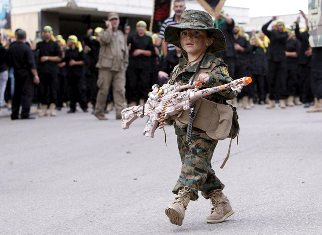 A boy wearing a Lebanon's Hezbollah military outfit and carrying a toy gun walks during the funeral of three Hezbollah fighters who were killed while fighting alongside Syrian army forces in Syria in Nabatieh town, southern Lebanon, October 27, 2015. (Photo by Ali Hashisho/Reuters)