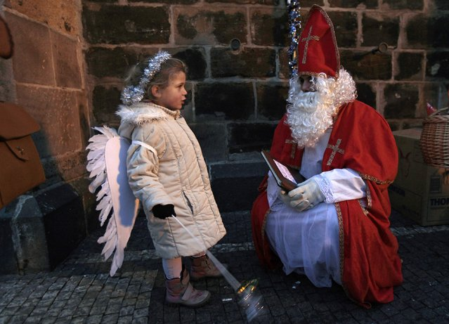 A child sings a song to a reveller dressed as Saint Nicholas at the Old Town Square in Prague, on the eve of Saint Nicholas Day December 5, 2014. (Photo by David W. Cerny/Reuters)