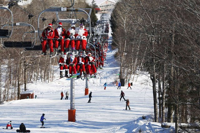 Skiers and snowboarders dressed as Santa Claus ride the chair lift to participate in a charity run down a slope at Sunday River Ski Resort in Newry, Maine December 7, 2014. (Photo by Brian Snyder/Reuters)