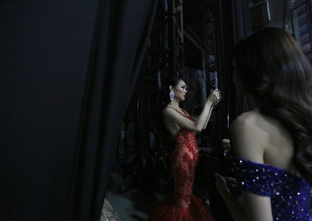 Contestant Yuko of Japan (L) prepares backstage during the annual transgender beauty contest of Miss International Queen 2018 at Pattaya city, in Chonburi province, Thailand, 09 March 2018. (Photo by Narong Sangnak/EPA/EFE)