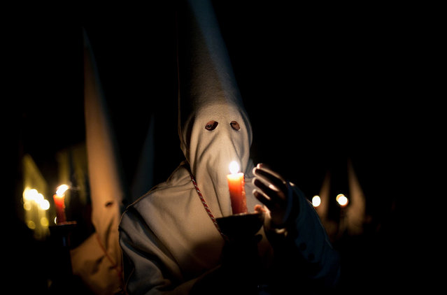 A penitent protects the flame of a candle during the Holy Week procession of the Cofradia Jesus Yacente on March 29, 2013 in Zamora, Spain. (Photo by Pablo Blazquez Dominguez /The Atlantic)