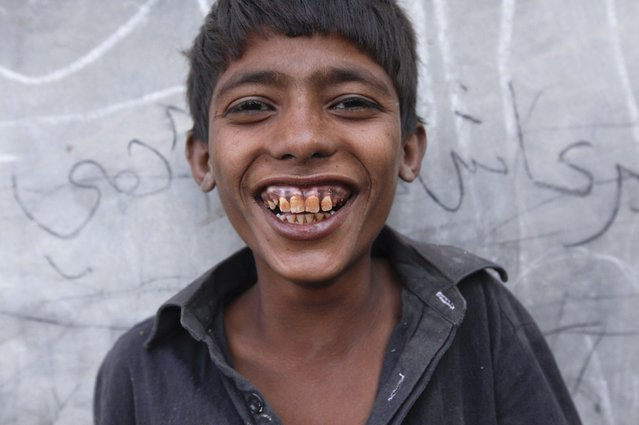 A boy who picks cotton from a field, smiles while being photographed along a street in Meeran Pur village, north of Karachi November 23, 2014. (Photo by Akhtar Soomro/Reuters)