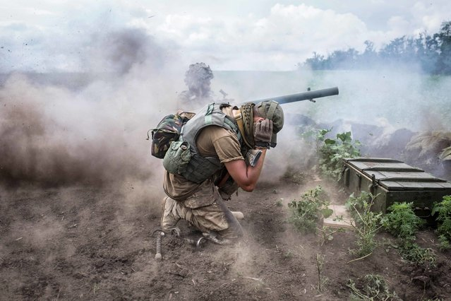 Ukraine, Shyrokyne: Linsa, his warname, shooting with the anti-tank grenade launcher. Next to him, his comrade Andrei is blocking his ears as the noise of the shooting is very high. Linsa is targeting some tanks that they have seen on the separatist side of Shyrokyne. June 26, 2015. (Photo by Virginie Nguyen Hoang)
