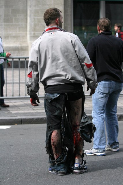 An injured man stands at the scene of an explosion at the Boston Marathon in Boston, Massachusetts, April 15, 2013. Two explosions struck the marathon as runners crossed the finish line on Monday, witnesses said, injuring an unknown number of people on what is ordinarily a festive day in the city. (Photo by Kenshin Okubo/Reuters/Daily Free Press/Boston University)