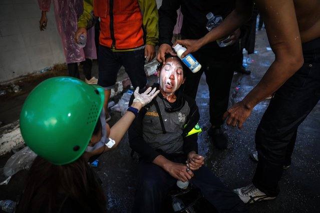 People assist a woman who was exposed to tear gas by pouring milk over her face after police fired tear gas and water canon to try and disperse protesters outside Parliament on November 17, 2020 in Bangkok, Thailand. The demonstrators gathered outside parliament, on Tuesday, as the Thai government met to discuss amendments to the country's constitution. (Photo by Lauren DeCicca/Getty Images)
