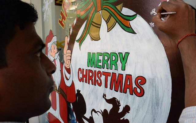 An Indian artist gives finishing touches to a Christmas-themed glass painting on the window of a showroom of electronics giant Sony in Mumbai on December 18, 2014. Even though Christians account for just over 2 percent of the billion plus strong Indian population Christmas is celebrated with great fervour in the country. (Photo by Indranil Mukherjee/AFP Photo)