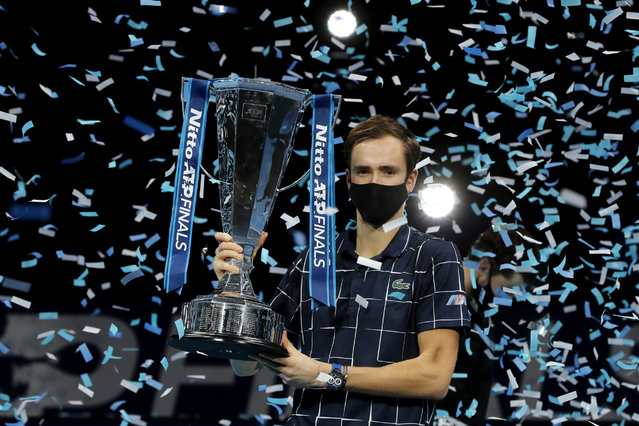 Daniil Medvedev of Russia holds up the winners trophy as confetti falls after defeating Dominic Thiem of Austria in the final of the ATP World Finals tennis match at the ATP World Finals tennis tournament at the O2 arena in London, Sunday, November 22, 2020. (Photo by Frank Augstein/AP Photo)
