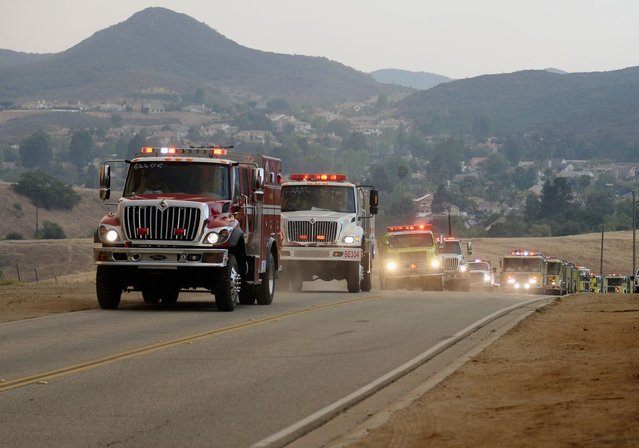 Fire trucks arrive to protect homes on Potrero Road as wildfire charges back up from Sycamore Canyon inside Pt. Mugu State Park on May 3, 2013 in Newbury Park, California. Hundreds of firefighters continue to battle wind and dry conditions with over 10,000 acres burned. (Photo by Kevork Djansezian/Getty Images)