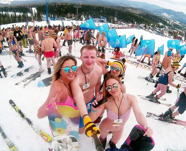 People in swimsuits participate in the Grelka Fest at the ski resort Sheregesh in Tashtagolsky District of Kemerovo Oblast, Russia on April 15, 2018. Skiers and snowboarders from around the world marked the end of the 2017-18 winter season. Wearing bikinis and bathing shorts a total of 1,525 claimed a new Russian record for the daring downhill escapade – in a temperature of around 5ºC. In fact, more have taken part in this GrelkaFest event in the past, but  not during an official record attempt. (Photo by Rodion Kirpichikov/The Siberian Times)