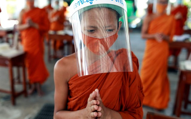 Buddhist novice monks wearing face shields and protective face masks attend a lesson at Wat Molilokayaram monastic educational institute during coronavirus disease (COVID-19) outbreak in Bangkok, Thailand on April 22, 2020. (Photo by Soe Zeya Tun/Reuters)