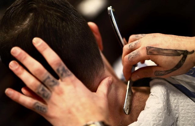 "Alex ""Torreto"" Vellios, a 26-year old Greek-born barber shaves the neck of a customer at his Torreto barber shop in Frankfurt January 6, 2015. (Photo by Kai Pfaffenbach/Reuters)"