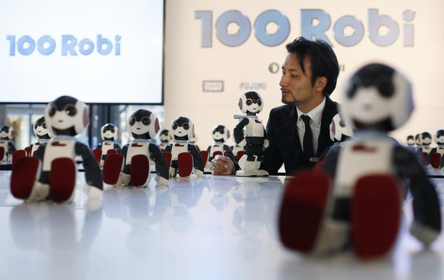 """Designer Tomotaka Takahashi speaks to his humanoid communication robots called """"Robi"""" during a promotional event called 100 Robi, for the Weekly Robi Magazine, in Tokyo January 20, 2015. (Photo by Yuya Shino/Reuters)"""