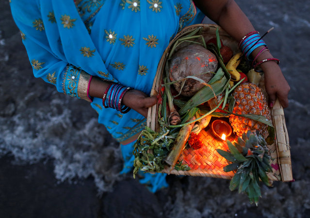 A Hindu devotee holds offerings as she worships the rising sun while standing in the waters of the Arabian Sea during Chhat Puja in Mumbai, India, November 7, 2016. (Photo by Danish Siddiqui/Reuters)